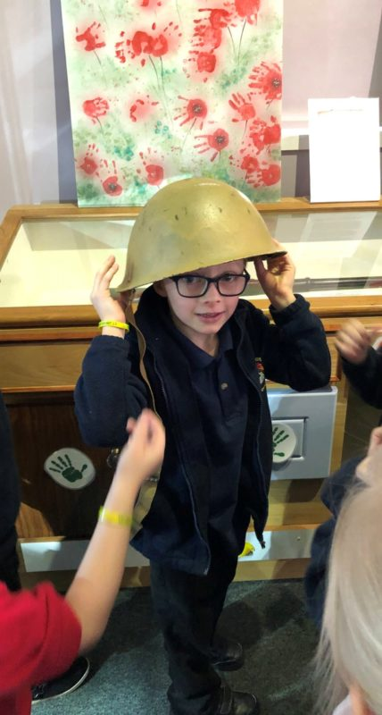 Photo of a child trying on a historic helmet