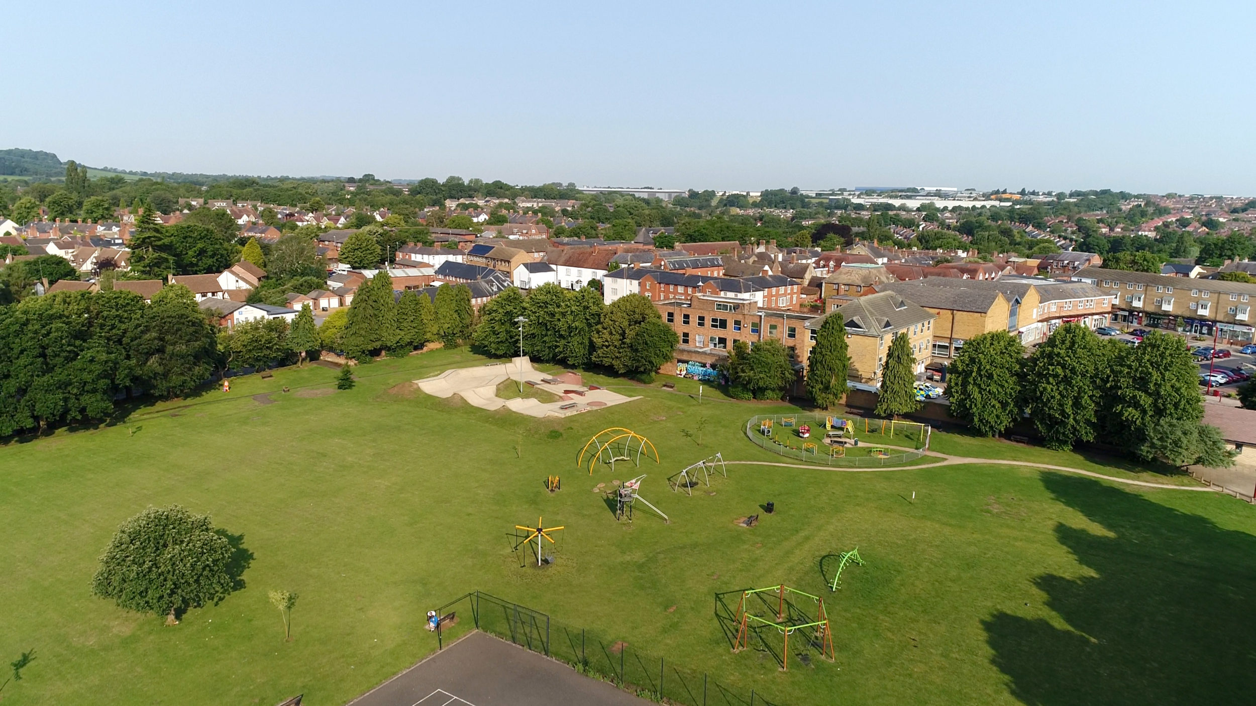 Aerial colour photograph showing a large green field with playground equipment and a skate park. The field is lined with trees, behind which are buildings and distant landscape