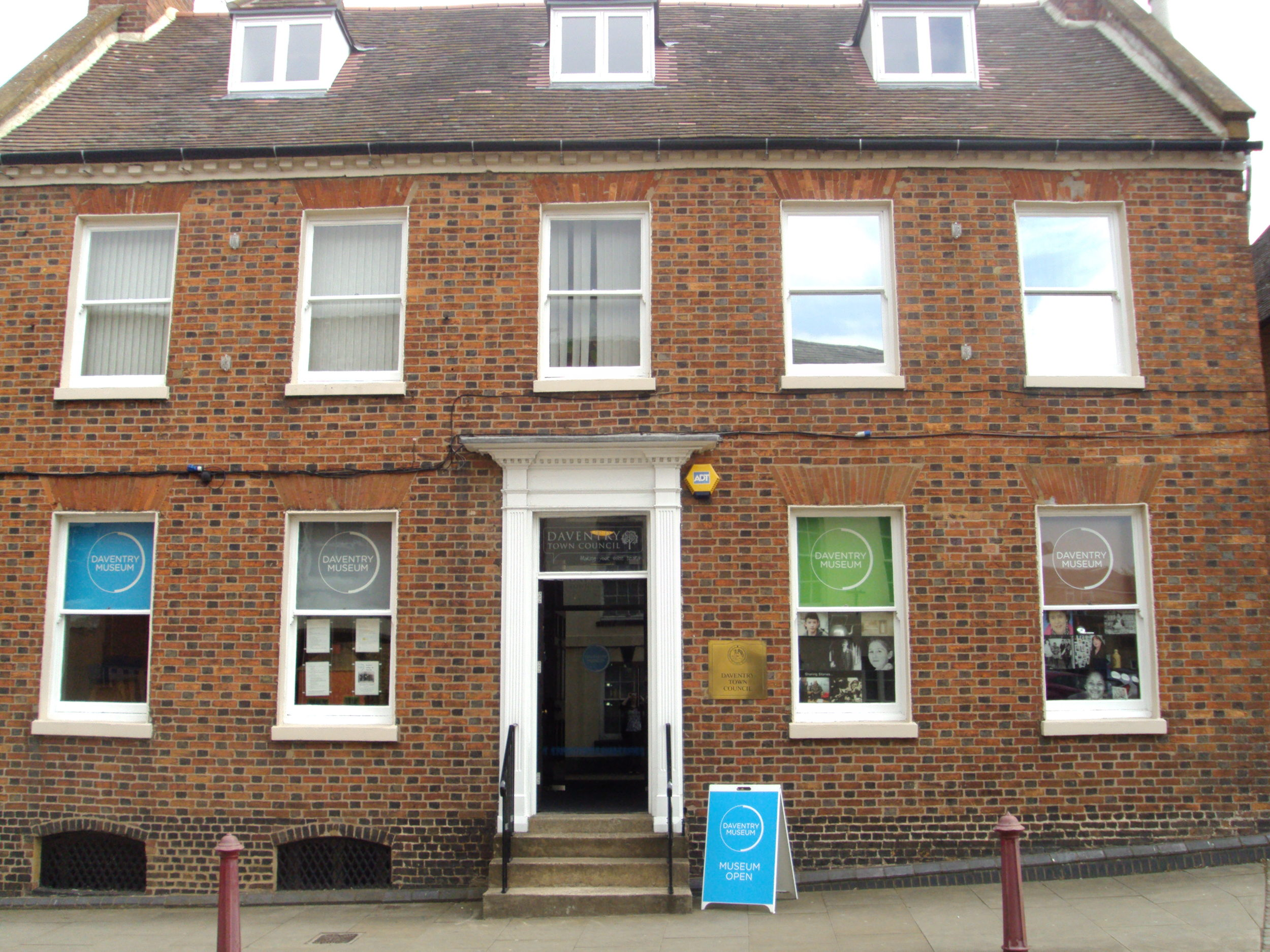 Photograph of a brown bricked, 3 storey building with Daventry Museum mid blue coloured a frame saying museum open. 4 windows on the ground floor display the museum logo on blue, grey, green and brown blinds