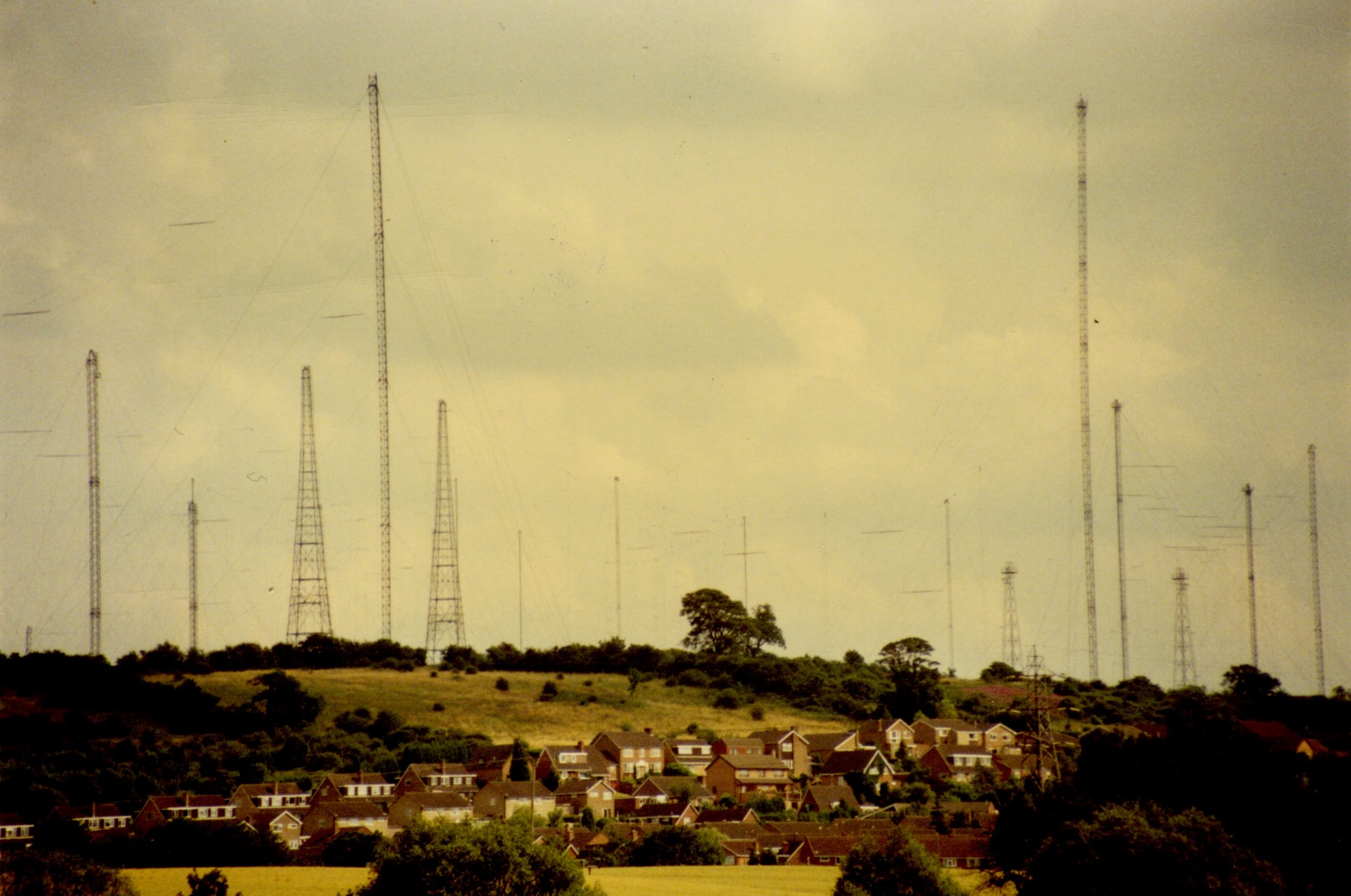 A photograph of a landscape featuring over 10 aerial masts and associated posts. The masts sit a top a hill with trees and bushes. At the bottom of the hill is a cluster of houses forming an estate.