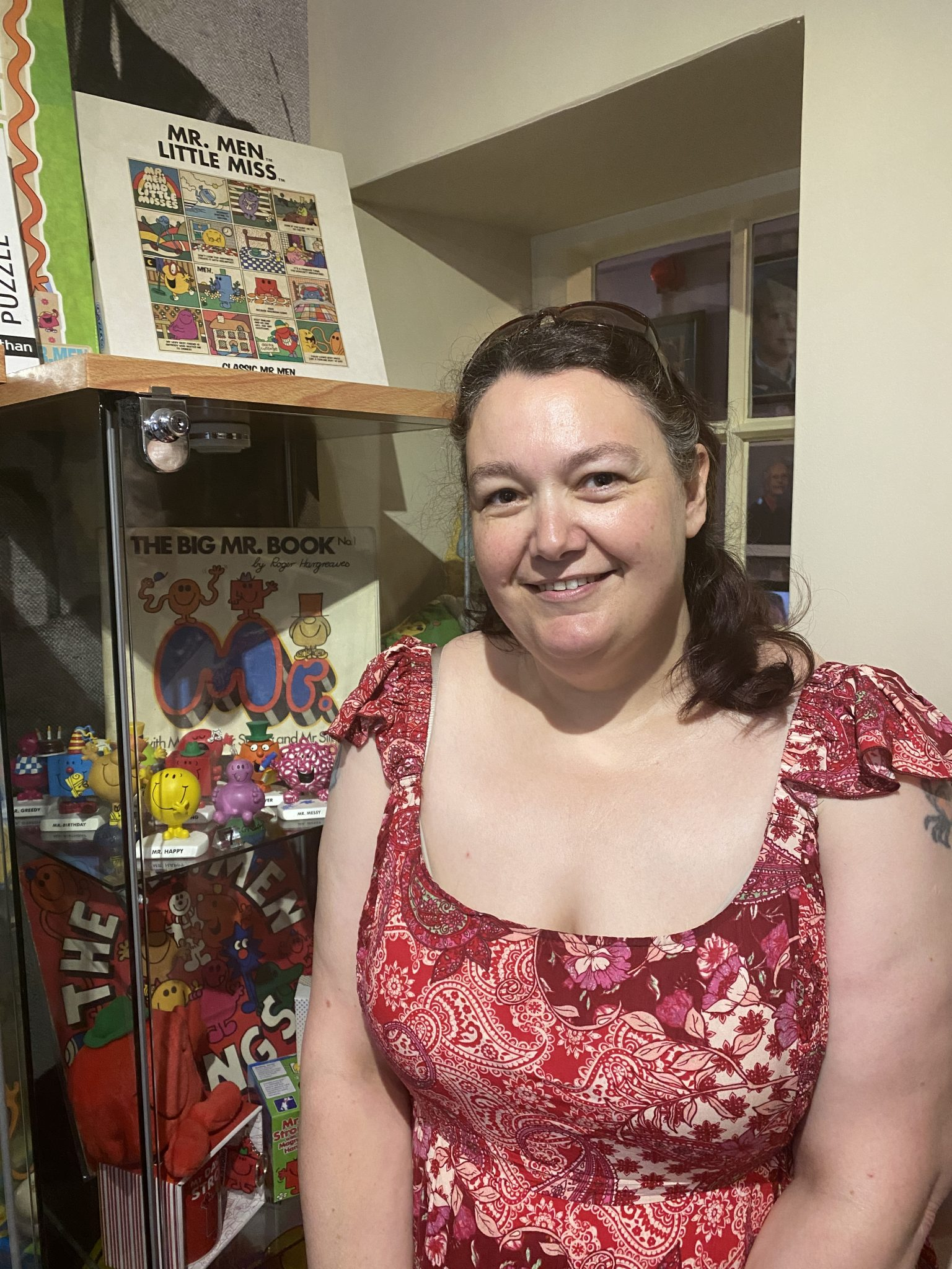 Photo of a person standing in front of a glass cabinet full of Mr Men figures.
