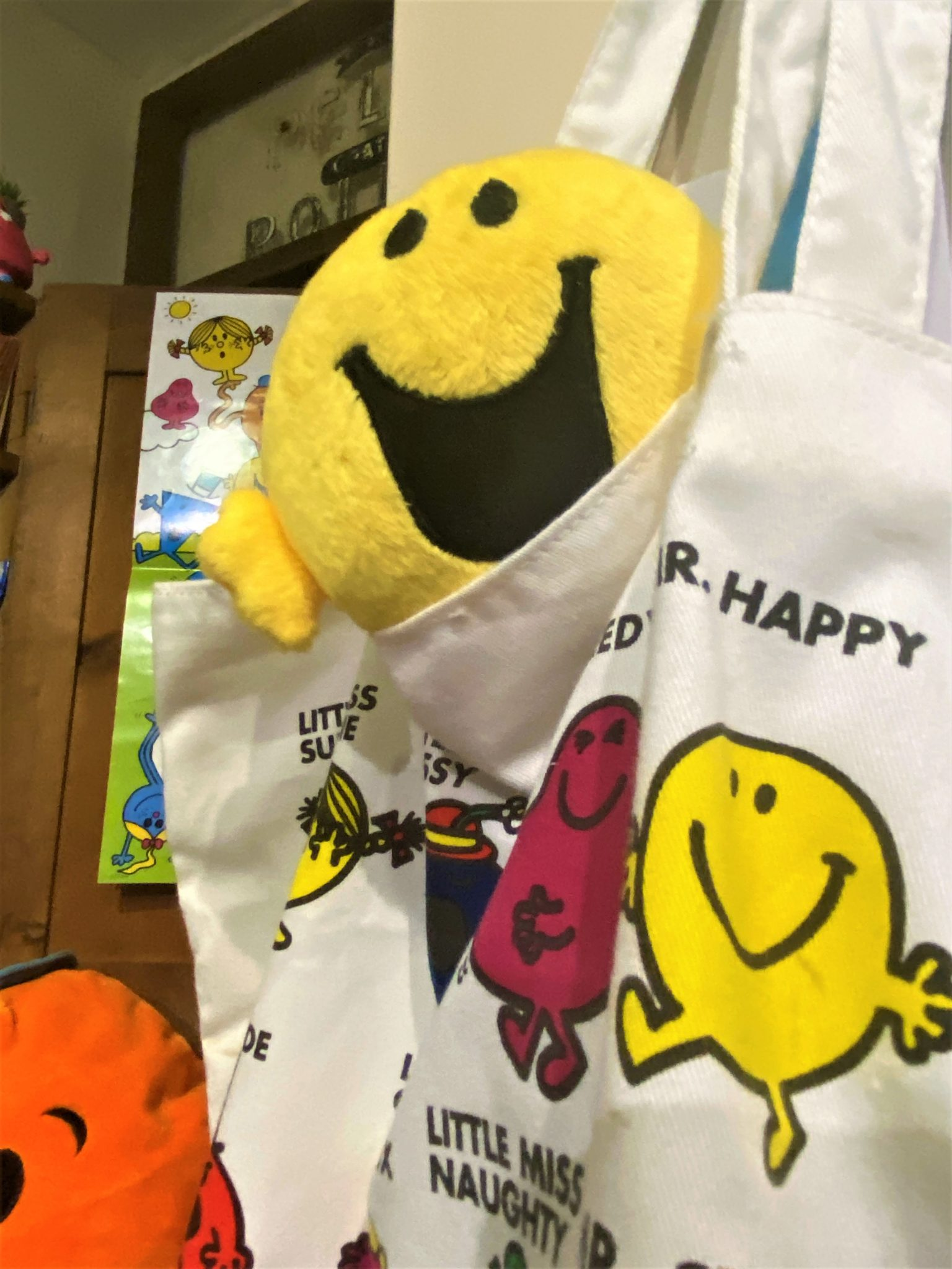 Photo of Mr Happy soft toy and colourful Mr Men fabric bag.