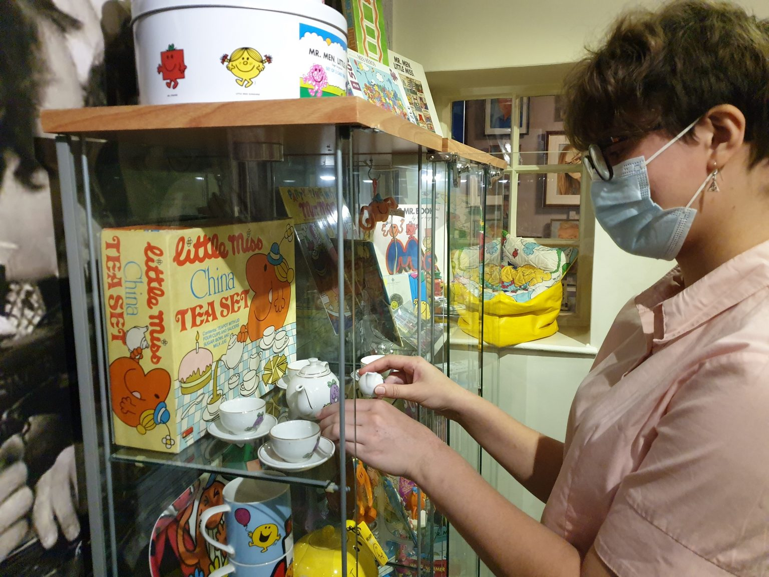 Photo of person arranging tea set in a glass cabinet.