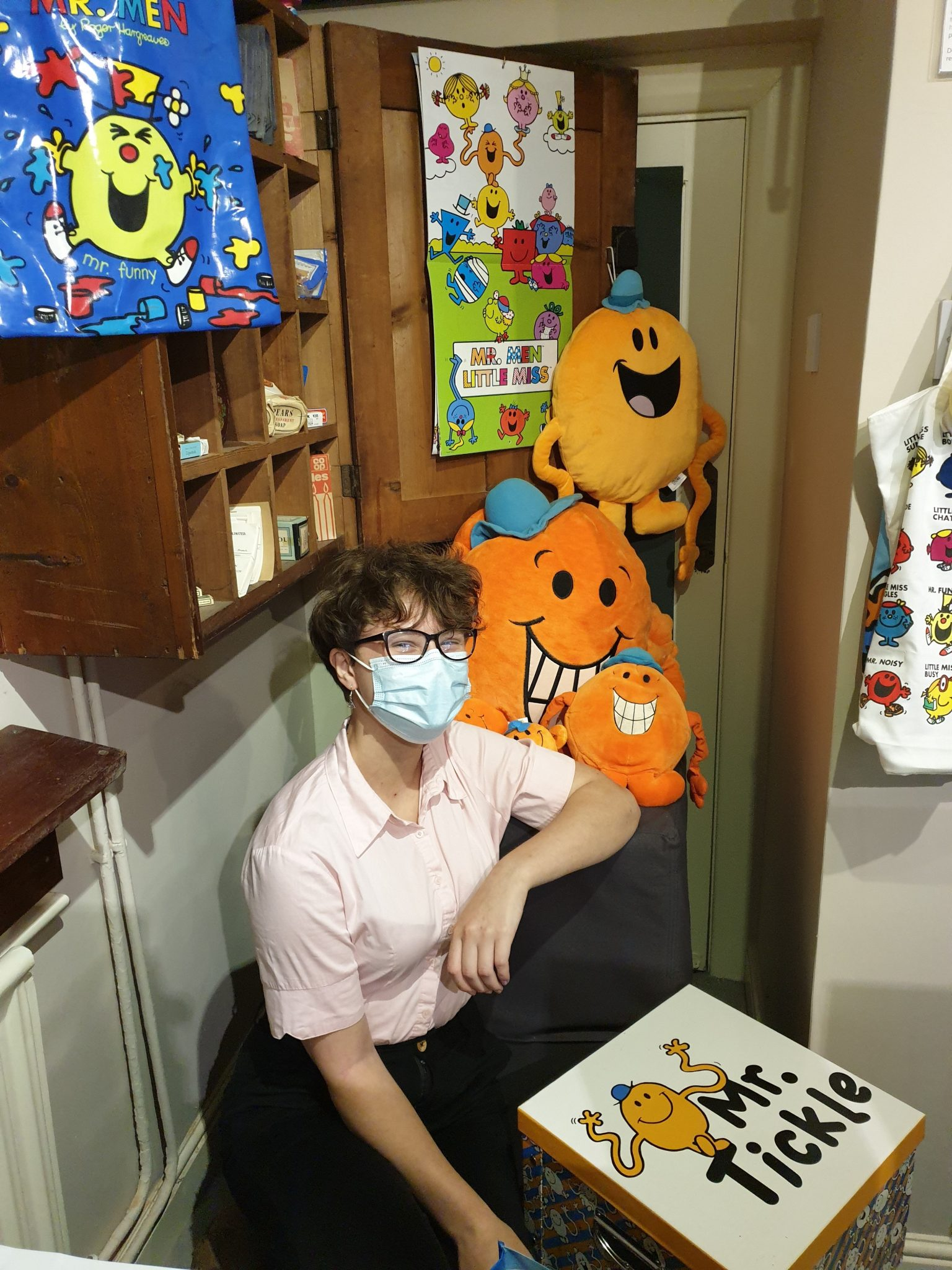 Photo of a person with lots of Mr Men soft toys and posters.