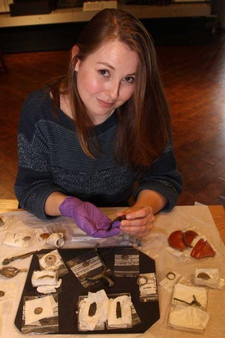 Colour photograph of a woman sitting at a table, with brown, mid length hair, wearing a purple glove and holding a small handle.  On the table are small archaeological finds.