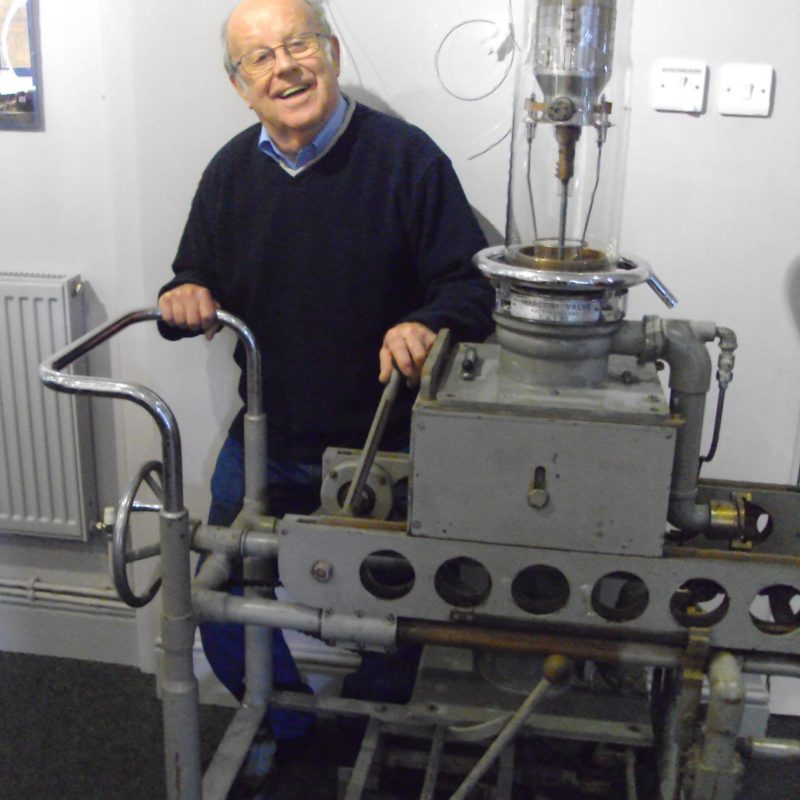 Colour photograph of a man demonstrating a metal valve trolley