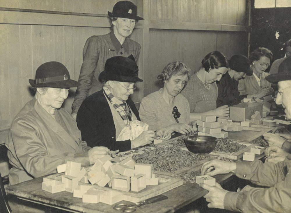 Black and white image showing people working around a table from war time.
